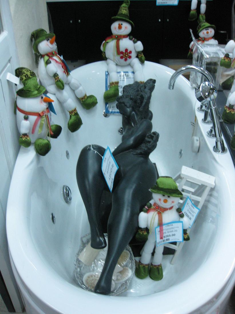 Again with the visual merchandising problems... A tub (wait, are we at Home Depot?) filled with a sculpture of a naked woman who's being stared down by multiple snowmen who have legs.